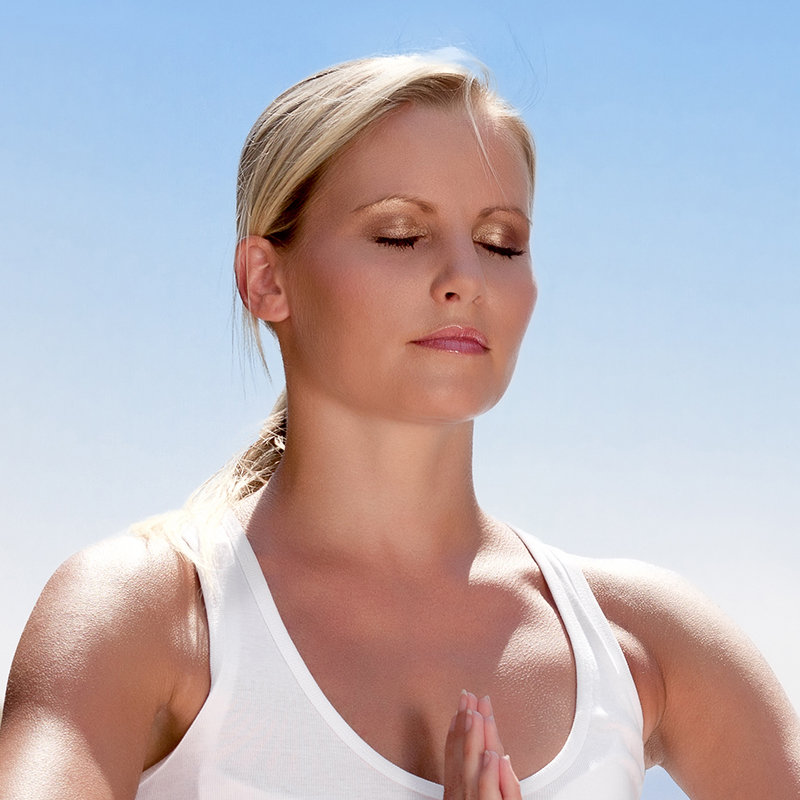 Beautiful positive girl clothing in white sit at the seaside on the rock and meditating in yoga pose