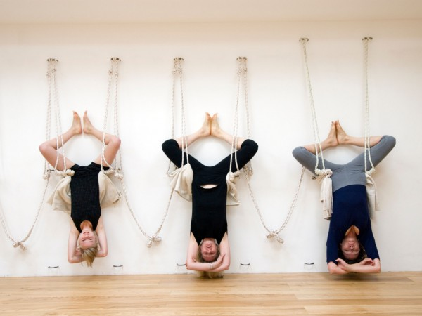 Women hanging upside down in yoga exercise at The Iyengar Yoga Studio, London, England, UK